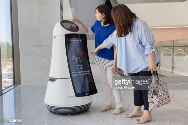 Two Korean women communicating with a Guide Robot from LG. The robot recognise language; In addition to English, it can also answer Korean, Chinese...