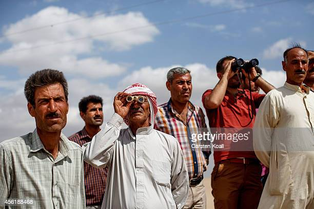 two Kurdish men look in a binoculars as Kurdish people from the region gather next to the borderfence to see the fighting between the Islamic State...