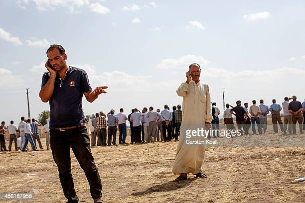 Two Kurdish men telephoned as Kurdish people from the region gather next to the borderfence to see the fighting between the Islamic State fighters...