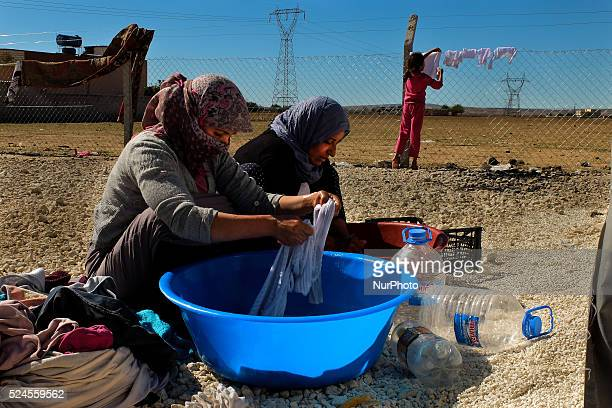 Two Kurds refugge women and a girl wash clothes in a refugee camp in the Turkish city of Suruc Sanliurfa province wich is located 6 kilometres far...