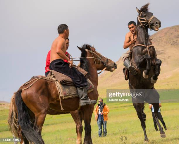 two kyrgyz wrestlers on horses and judge during on birds or prey festival, kyrgyzstan - match point scoring stock pictures, royalty-free photos & images