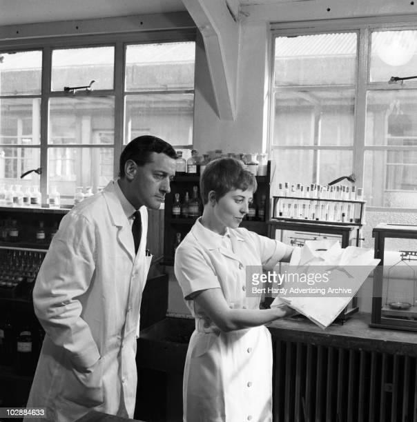 Two laboratory technicians examining shirts, 31st May 1961.