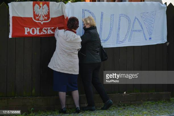 Two ladies are fixing a hand made election poster of Andrzej Duda the current President of Poland and a candidate for the Presidential Election 2020...