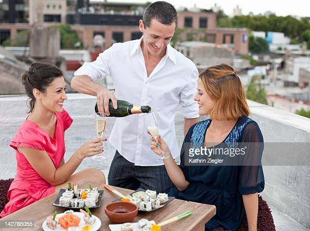 two ladies being served sushi and champagne