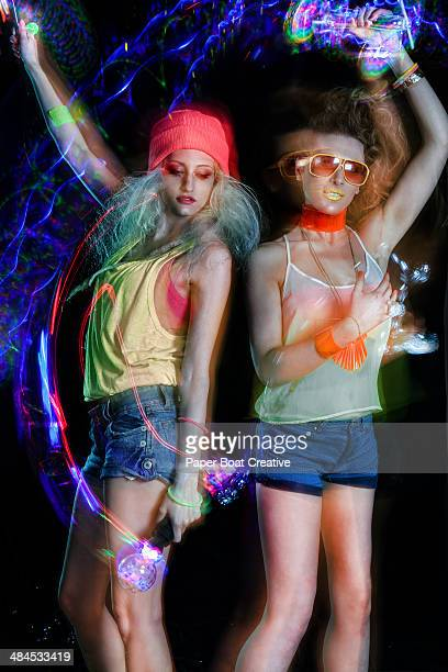 Two ladies dancing with strobe lights at club