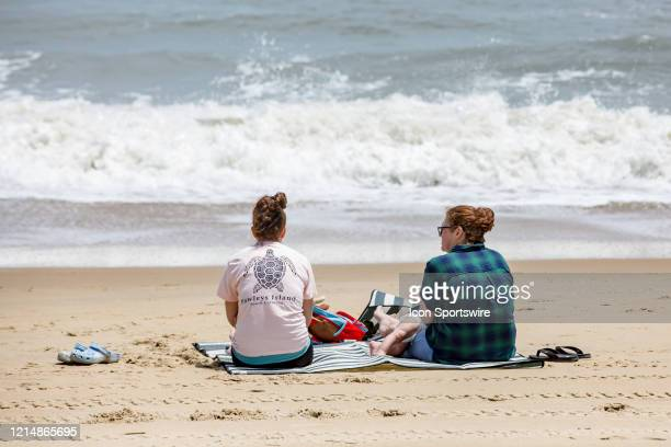 Two ladies enjoy sitting on the beach to kick off Memorial Day weekend on May 22 in Virginia Beach VA This is the first day of the beach's reopening...