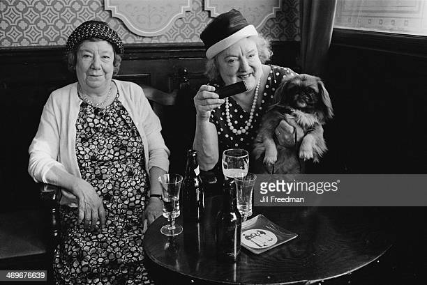 Two ladies enjoying a beer in a London pub 1969 The woman on the right is holding her dog and a harmonica