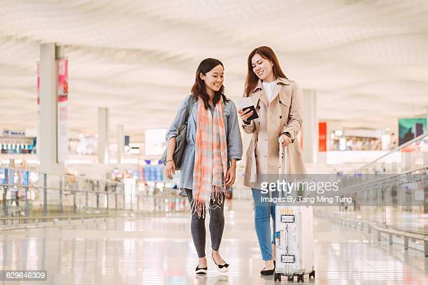 Two ladies looking at passport at airport