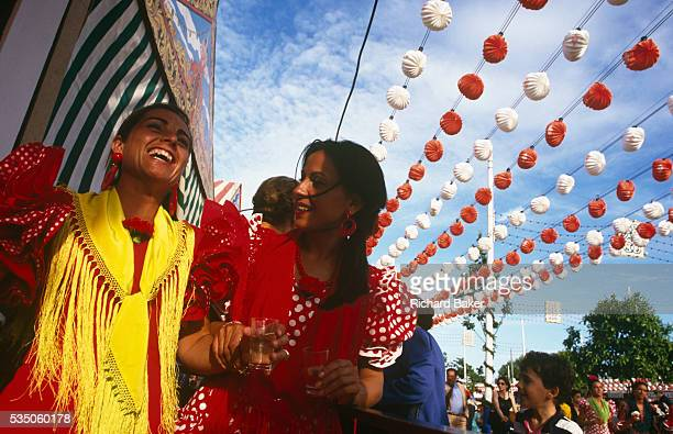Two ladies parade down an avenue during the Spring Feria in Seville Spain Beneath dozens of colourful decorations which hang from cables above their...