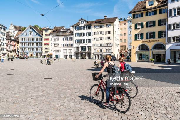 two ladies ride bikes in town square in zurich - zurich stock photos and pictures