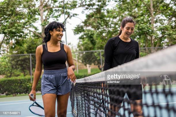 two ladies shaking hands after tennis match - tennis tournament stock pictures, royalty-free photos & images