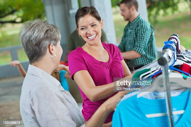 two ladies shopping or donating second hand clothing - garage sale stock pictures, royalty-free photos & images