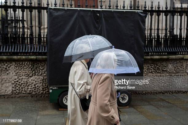 Two ladies use transparent umbrellas during heavy rainfall on an autumn afternoon outside St MartinintheFields church on Trafalgar Square on 24th...