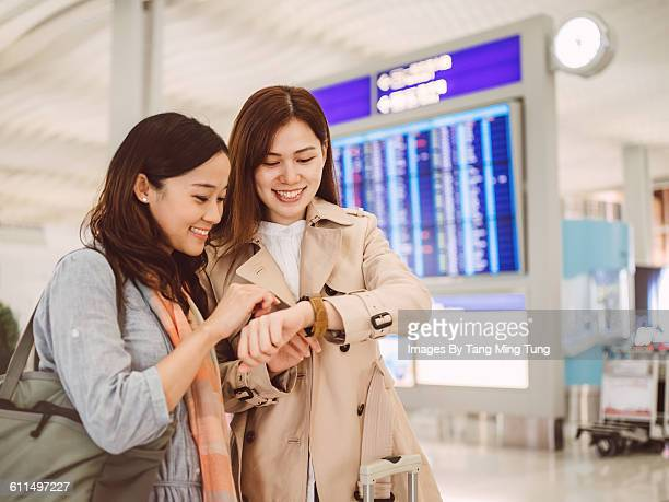 Two ladies using smart watch at airport