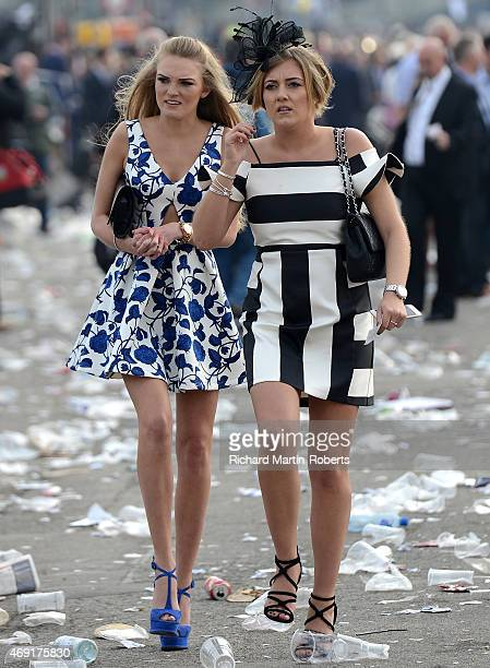 Two Ladies walk through debris on Day 2 of the Aintree races at Aintree Racecourse on April 10 2015 in Liverpool England