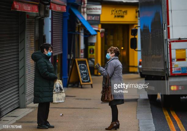 Two ladies wearing face masks chat in the street in Dublin city center on the eve of St Patrick's Day during Level 5 Covid-19 lockdown. On Tuesday,...