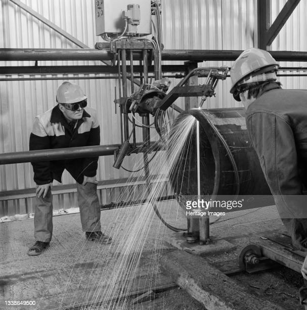 Two Laing workers at Graythorp watching a precision tool cutting through a large metal tube. In the early 1970s Laing Pipelines Offshore constructed...