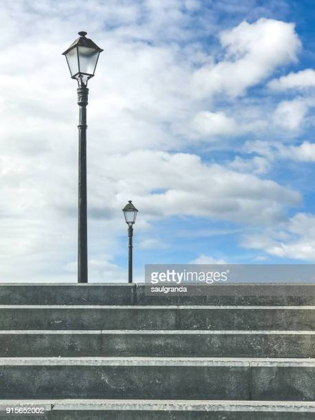 Two lampposts against the sky
