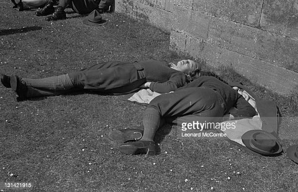 Two Land Girls sleeping in the sun after completing a march in the West Sussex Land Girls' rally at Arundel Castle West Sussex 29th May 1943 Original...