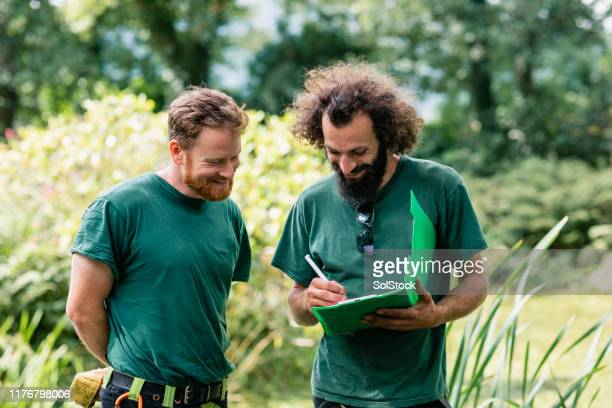 two landscape gardeners making notes on clipboard - landscaped stock pictures, royalty-free photos & images