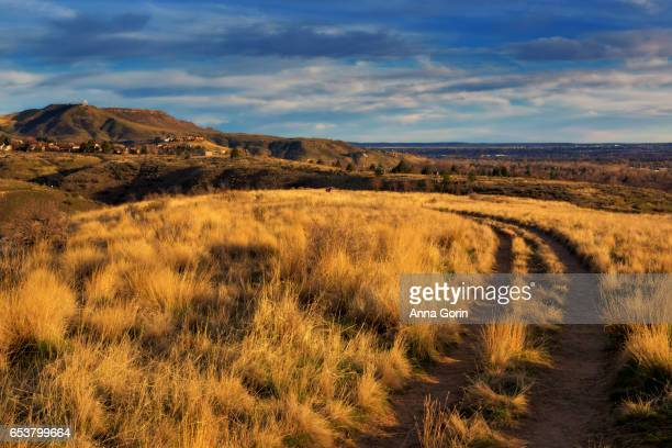 Two lane dirt path through golden foothills with iconic Table Rock in background, spring in Boise, Idaho