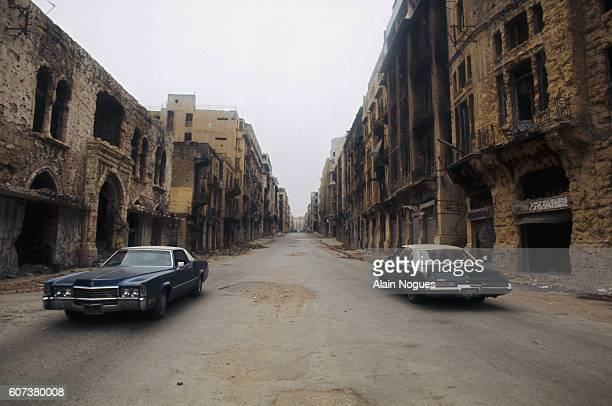 Two large American cars roll through a deserted Beirut street. The fifteen year long civil war did massive damage to the city.