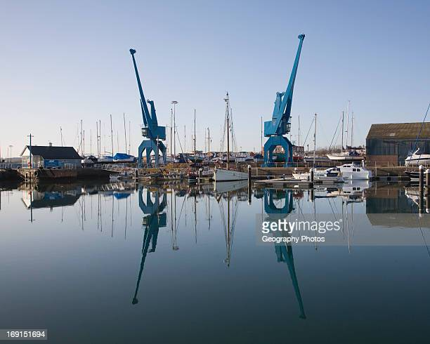 Two large blue industrial cranes reflected in water of Wet Dock marina, Ipswich, Suffolk, England.
