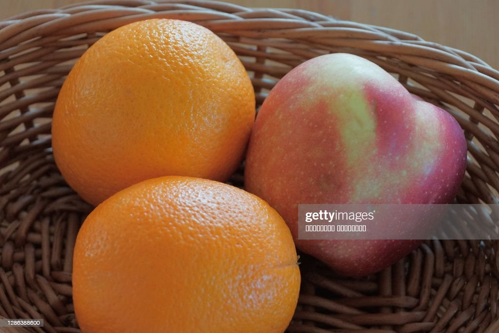 two large oranges and an apple : Stock Photo