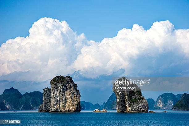 Two large rock structures in Halong Bay under fluffy clouds