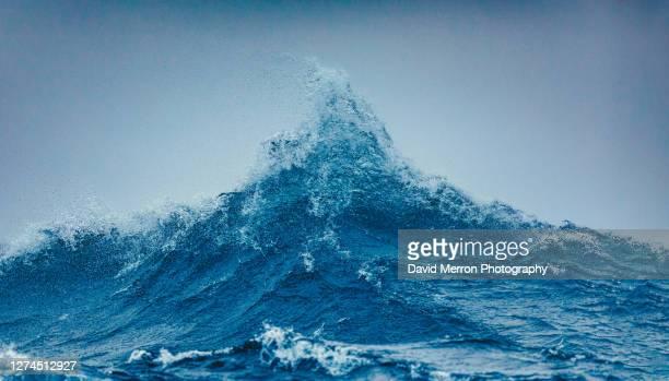 two large swells meet and create a large peak of powerful ocean - marea fotografías e imágenes de stock
