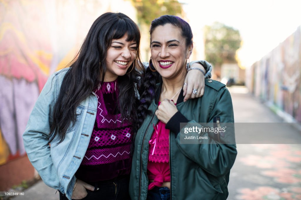 Two Latina Friends Laughing While Standing in Mural Alley in San Francisco's Mission District : Stock Photo