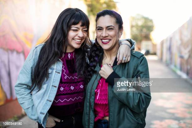 two latina friends laughing while standing in mural alley in san francisco's mission district - mission district stock photos and pictures