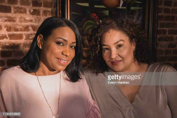 Two Latina moms looking at camera, sitting at dinner table.