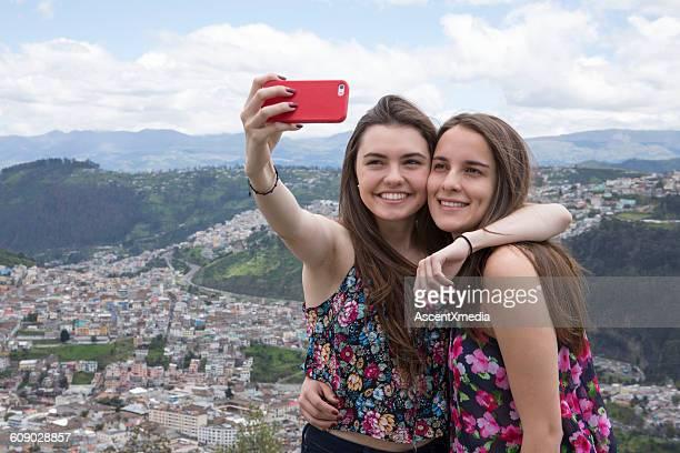 2人のラティーナの女性が街の上で自分撮りをする - キト ストックフォトと画像
