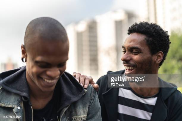 Two latino african male friends laughing