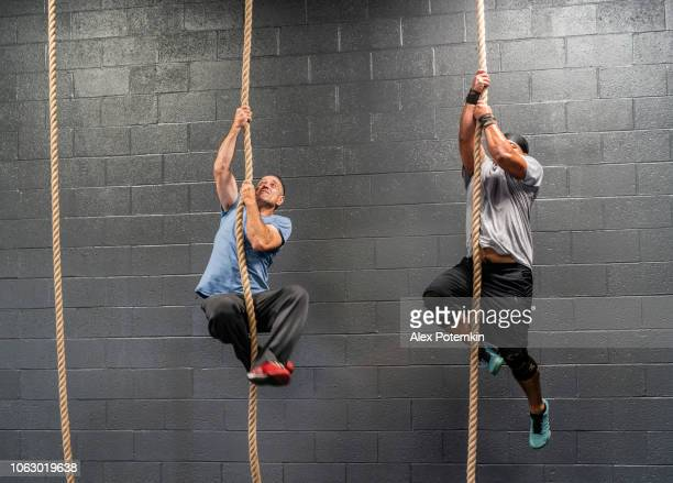Two Latino athletes, the senior, 55-years-old, coach, and the young man climbing by a rope during the workout
