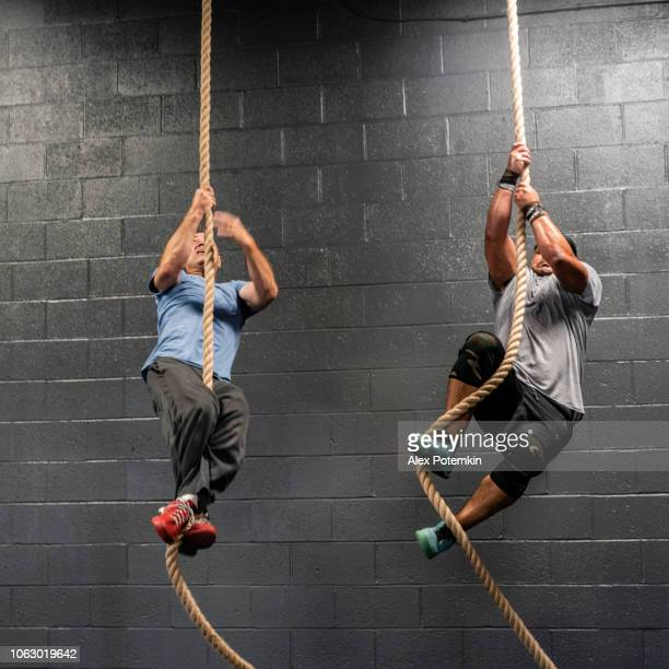 two latino athletes, the senior, 55-years-old, coach, and the young man climbing by a rope during the workout - alex potemkin or krakozawr latino fitness stock photos and pictures