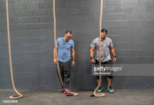 two latino athletes, the senior, 55-years-old, coach, and the young man preparing to climbing by a rope during the workout - alex potemkin or krakozawr latino fitness stock photos and pictures