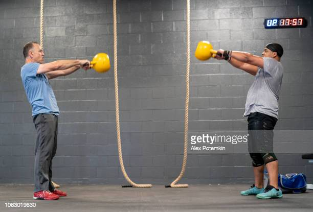 Two Latino athletes, the senior 55-years-old coach, and the younger man, doing the Russian Cannonball exercise with the heavyweight kettlebell.