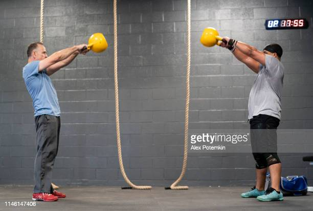 two latino athletes, the senior 55-years-old coach, and the younger man, doing the russian cannonball exercise with the heavyweight kettlebell. - 55 59 years stock pictures, royalty-free photos & images