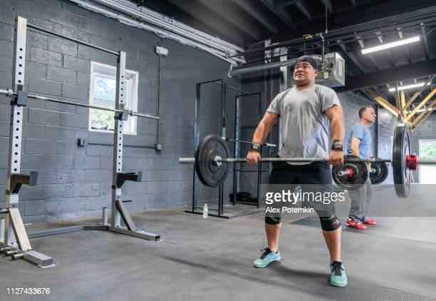 two latino athletes, the young man on the front, and the senior 55 years old man in the backstage, lifting heavy weights in the gym - alex potemkin or krakozawr latino fitness stock photos and pictures