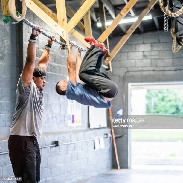 two latino men, the senior coach, and the young athlete, pulling-up on the horizontal bar in the gym during the hard workout - alex potemkin or krakozawr latino fitness stock photos and pictures