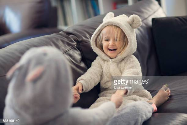 two laughing children playing 'row your boat' game on a sofa - nur kinder stock-fotos und bilder
