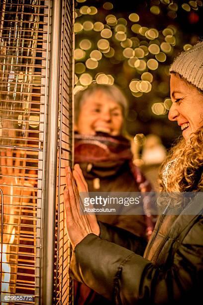 2人の笑う女性の友人と火、夜、クリスマス、ケルンシア、オーストリア - クラーゲンフルト ストックフォトと画像