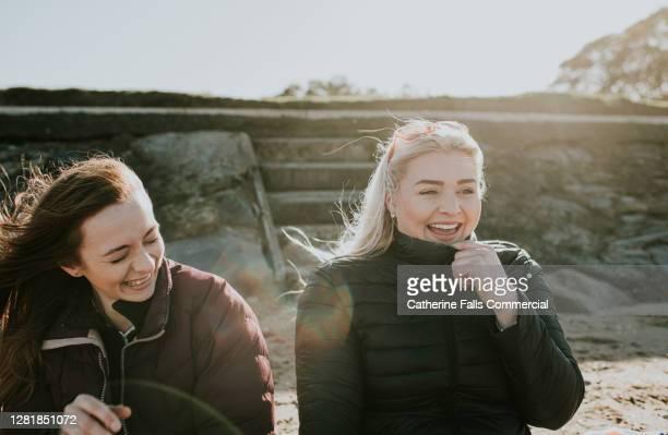 two laughing female friends on coats sit on a beach on a windy day. - warm clothing stock pictures, royalty-free photos & images