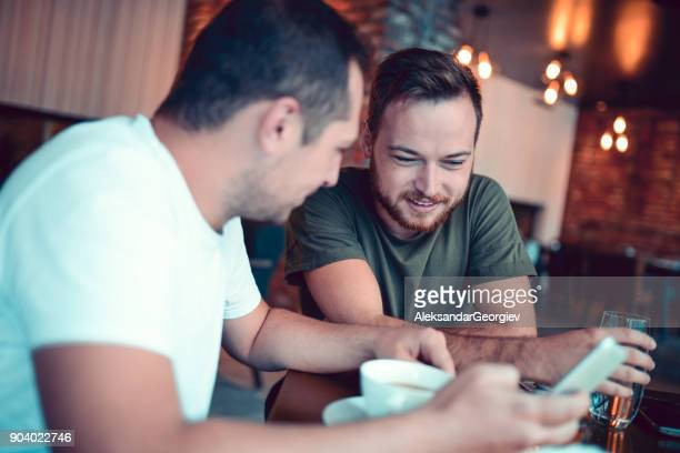 Two Laughing Friends looking at Smartphones In a Cafe Restaurant