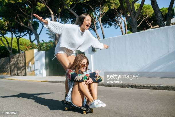 two laughing friends together on skateboard - women in harmony stock pictures, royalty-free photos & images