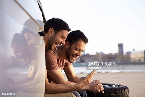 Two laughing men sitting in car looking at digital tablet