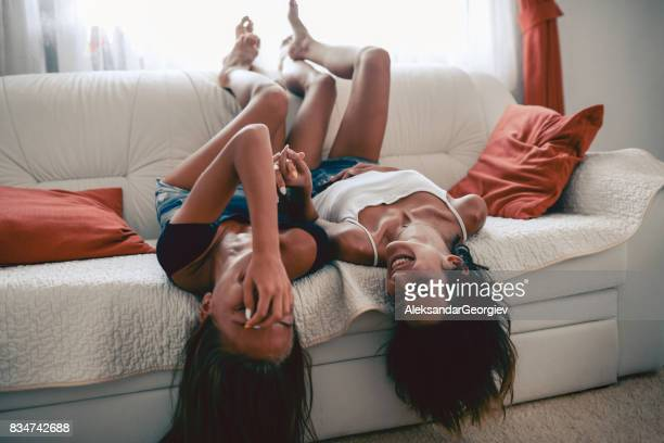 Two Laughing Sensual Females Lying on Sofa and Holding Hands