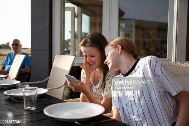 two laughing teenage girls sitting at an outdoors dining table looking at a mobile phone - denmark stock pictures, royalty-free photos & images